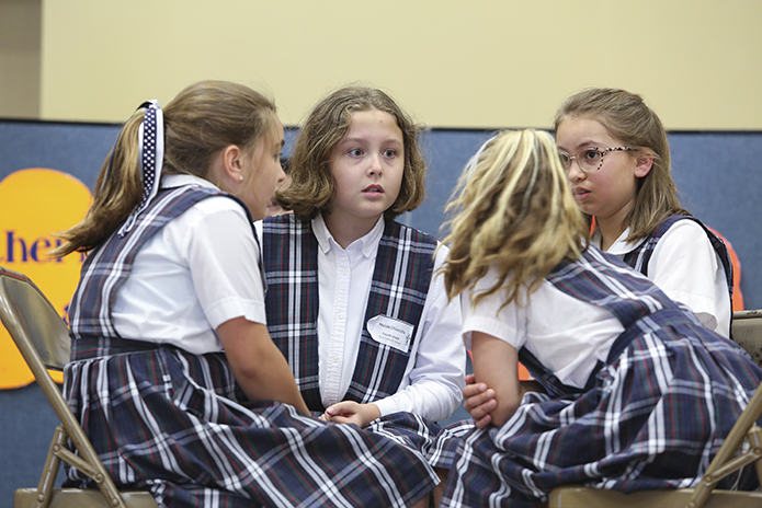 From afar the discussion between Our Lady of the Assumption School teammates cannot be heard, but sometimes the eyes speak volumes. In this instance, Claire Schepp, Nicole Chinchilla. Ella Weber and Cate Prophater dialogue during the fourth-grade finals as they ponder the answer to a question. Photo By Michael Alexander