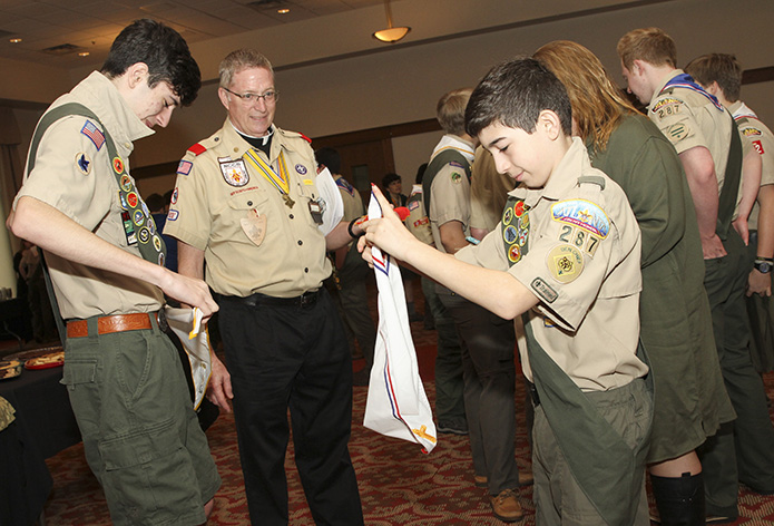 Deacon Tom Ryan, second from left, the chaplain for St. Catherine of Siena Church's Troop 422, watches as Thomas Kent, left, and his younger brother, Matthew, of St. Joseph Church's Troop 287, Marietta, prepare their neckerchiefs before the March 24 Atlanta Archdiocesan Scout Mass. Photo By Michael Alexander