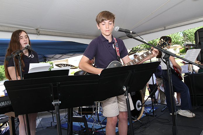 St. Catherine of Siena School praise band members included eighth-grader Charlie Smith, center, on guitar, seventh-grader Samantha Gregory on keyboards, left, her sister Sarah on bass, right, and William Collins on drums. They performed for various students under a tent on the school parking lot during the Faith Rally. Photo By Michael Alexander