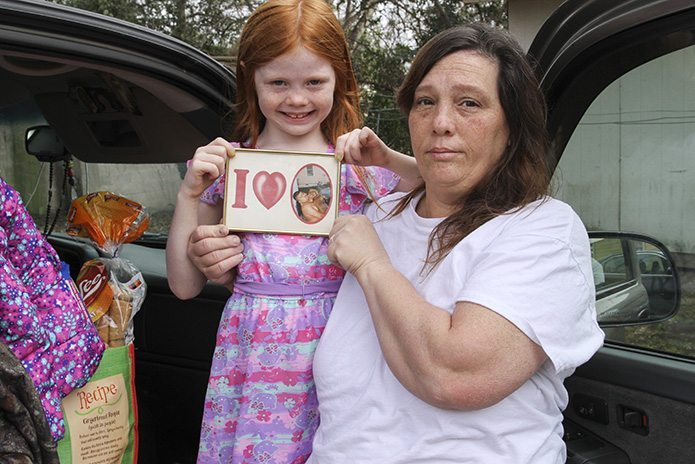Melissa Sandoval and her 6-year-old granddaughter Hailee hold a photo of Melissa's husband Domingo, a Mexican detainee, as they prepare to leave El Refugio after an overnight stay. After loading the truck with their belongings, they were planning to stop by the Stewart Detention Center to visit Domingo before driving back to Rome, Ga. Photo By Michael Alexander