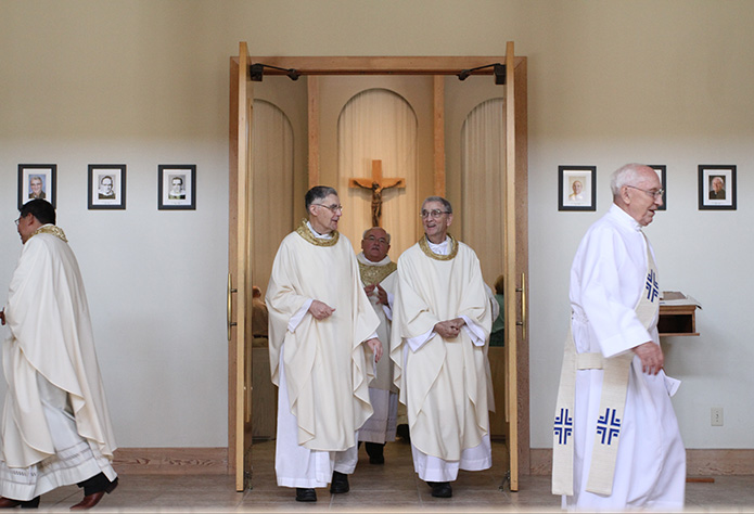 Two of Holy Cross Church's former pastors, Msgr. Paul Fogarty, left center, and Father Ed O'Connor, right center, exit the sanctuary following the 50th anniversary Mass honoring its founders and former pastors. Father O'Connor was the homilist for the July 26 liturgy. Photo By Michael Alexander