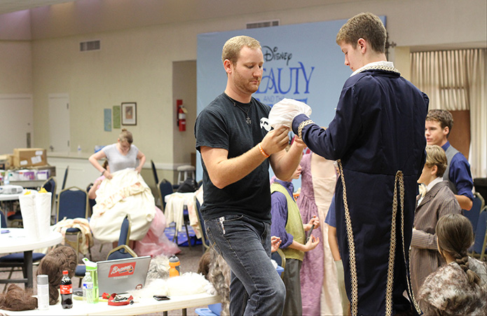 Matthew Thornton, left, director and choreographer for the production of Disney's Beauty and the Beast Jr., makes some costume adjustments for Spencer Lail, who is cast as the Beast and Prince. The proceeds from the three productions, the weekend of July 18-20, benefited the parish's St. Martin de Porres food pantry. Photo By Michael Alexander