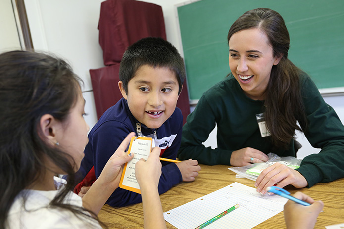 Brittany Anderson, right, conducts an exercise about U.S. states and capitols with second-graders Jesus Salina, center, and Abril Osorio. Anderson, a University of Georgia graduate student pursuing a master's degree in education, started tutoring at the beginning of the 2014 spring semester. Photo By Michael Alexander