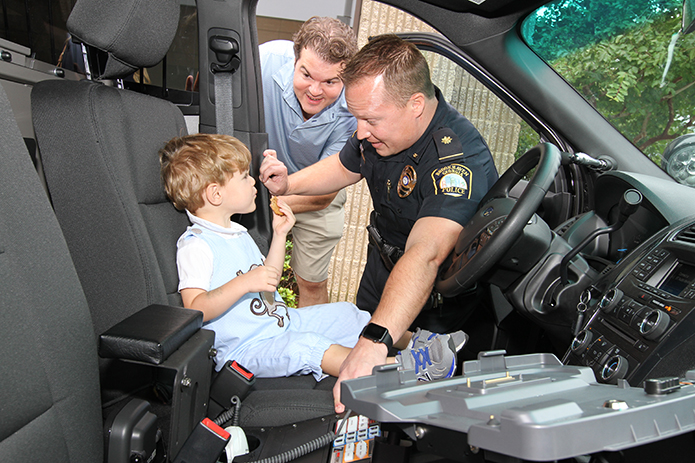 (Clockwise, from right) Brookhaven Police Department's Major Brandon Gurley allows 2-year-old Thomas Gioia to sit behind the steering wheel of the Police Interceptor SUV, as his father Tom looks inside. Tom's wife Ashlyn and his 4-year-old daughter, Eleanor, also came to the police station to visit Major Gurley. Photo By Michael Alexander