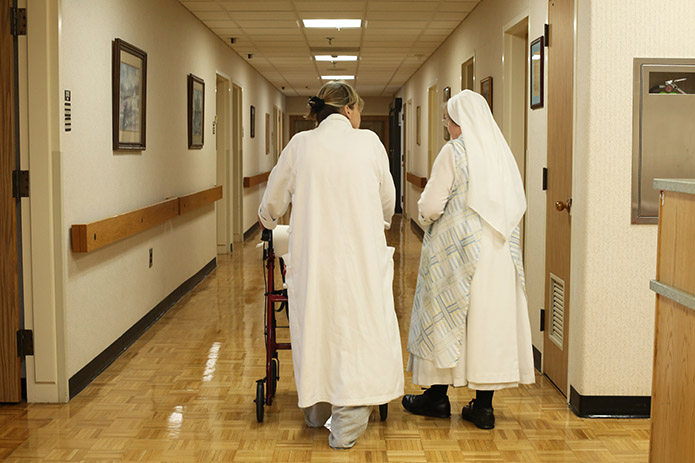 Patient Pamela Hughes, left, returns to her second floor room, accompanied by Hawthorne Dominican Sister Mary Kateri. Photo By Michael Alexander