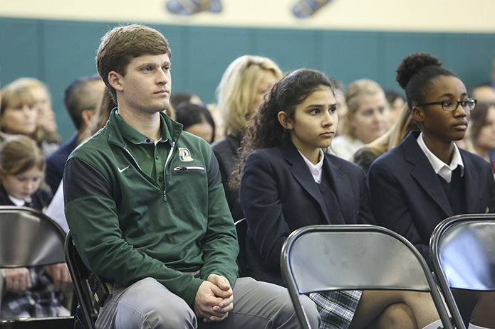 (L-r) Jonathon Oshinski, Pinecrest Academy middle school P.E. teacher and middle school boys basketball coach, sits with eighth-graders, Gabi Rodriguez and Jada Green, during the Feb. 2 Founder's Day Mass. Oshinski is 2010 graduate of Pinecrest Academy. Photo By Michael Alexander