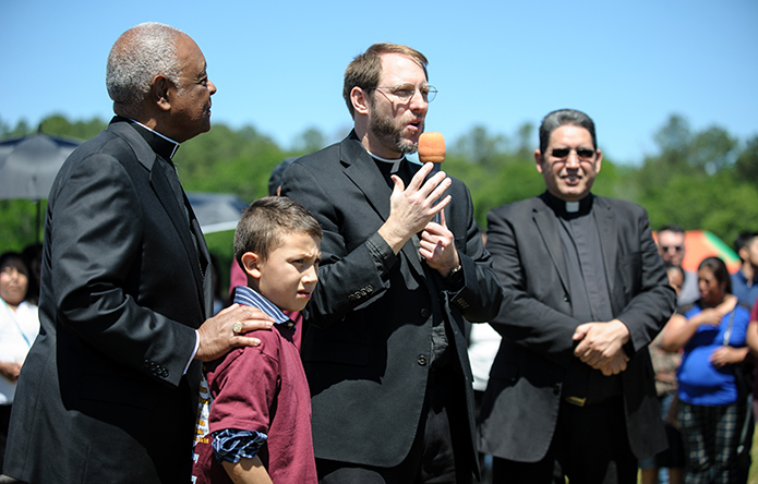 Father Timothy Gallagher, pastor of St. Bernadette Church, invites 8-year-old Tony Pizano to join Archbishop Gregory and building committee members for the official groundbreaking of a new parish center. Deacon Jose Orellana is shown right. Photo By Gibbs Frazeur
