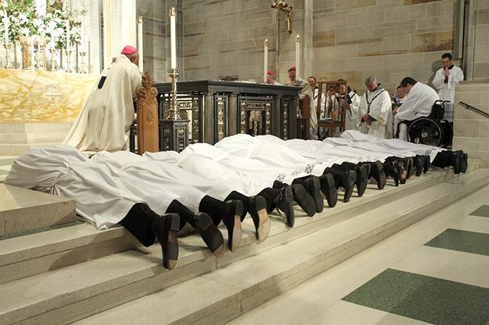 The twelve ordination candidates prostrate themselves on the altar at the Cathedral of Christ the King during the Litany of the Saints. Photo By Michael Alexander