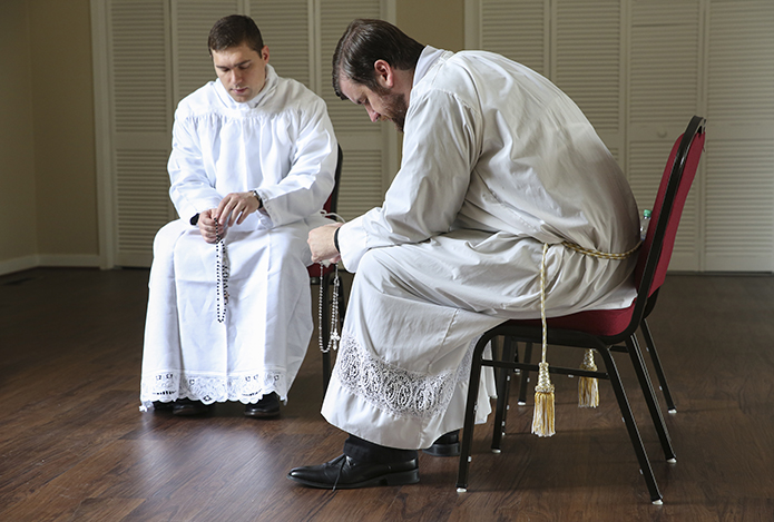 In the solitude of the ministry offices building at the Cathedral of Christ the King, Atlanta, Rev. Mr. Bryan Kuhr, left, and Rev. Mr. Bradley Starr pray the Joyful Mysteries of the rosary before their June 24 ordination to the priesthood. Photo By Michael Alexander