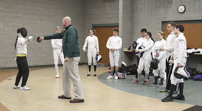 As members of the team look on, Pinecrest Academy head fencing coach Chad Morris, foreground in green jacket, demonstrates why distance matters during fencing with senior fencer Claire Rivard. Practice is held at the Old Atlanta Recreation Center in Suwanee. Photo By Michael Alexander
