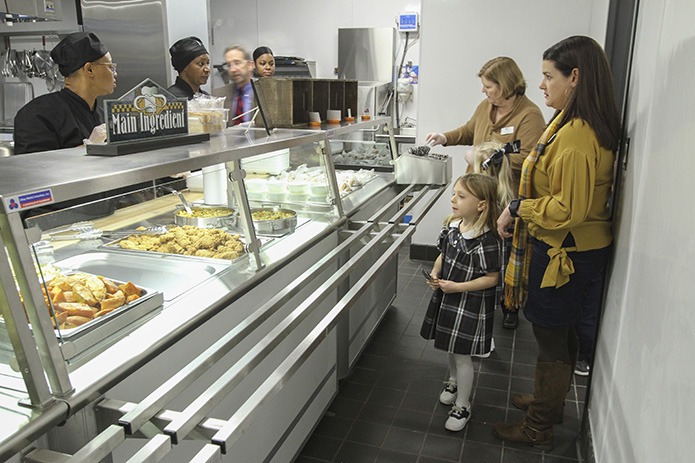 As principal Lisa Cordell, background right, passes out utensils to students, Sienna Smith is the first student to go through the food line, accompanied by her kindergarten teacher Karen Cosse. The new cafeteria was up and running for students and teachers on Nov. 29. Photo By Michael Alexander