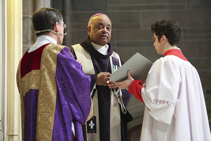 Joining Archbishop Wilton D. Gregory, center, on the altar are Deacon Tom Gotschall, left, chaplain for the Archdiocesan Catholic Committee on Scouting, and alter server Michael Marcinko, an Eagle Scout from the Cathedral of Christ the King's Troop 74. Photo By Michael Alexander