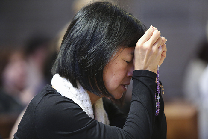 Sharon Mai of St. Benedict Church, Johns Creek, joins the congregation in praying the joyful mysteries of the rosary prior to the Mass for the Unborn. Photo By Michael Alexander.