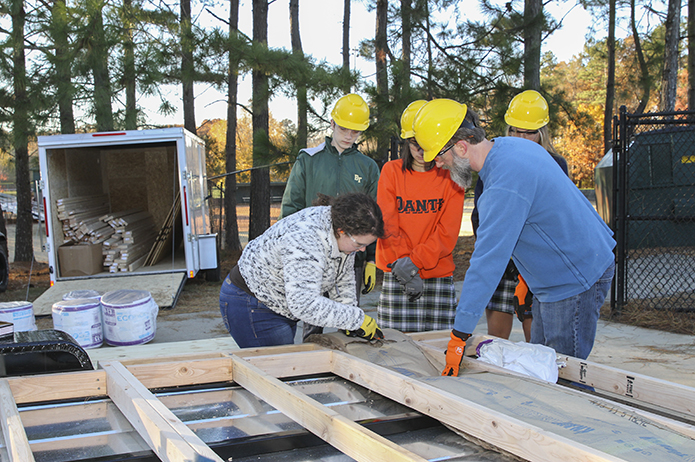 Senior Rosie Nemec, foreground left, cuts the insulation to fit properly between the wood beams of the sub-floor. Assisting from the right is Jason Podhorez, project manager and the school's computer systems administrator. Photo By Michael Alexander