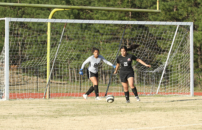 After a failed scoring attempt by Atlanta Classical Academy, Our Lady of Mercy defender Mely Moncayo (#21) looks to get the ball out of the area and up the field. Looking on from behind is Our Lady of Mercy goalie Kaila Pouncy. Photo By Michael Alexander