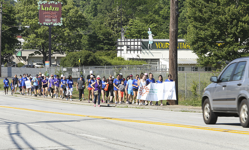 The walkers make their way up East Ponce de Leon Avenue to the Dekalb Farmers Market, the second mile of their five-mile journey. The pilgrimage started at St. Thomas More Church, Decatur, and ended at Refuge Coffee in Clarkston. Photo By Michael Alexander