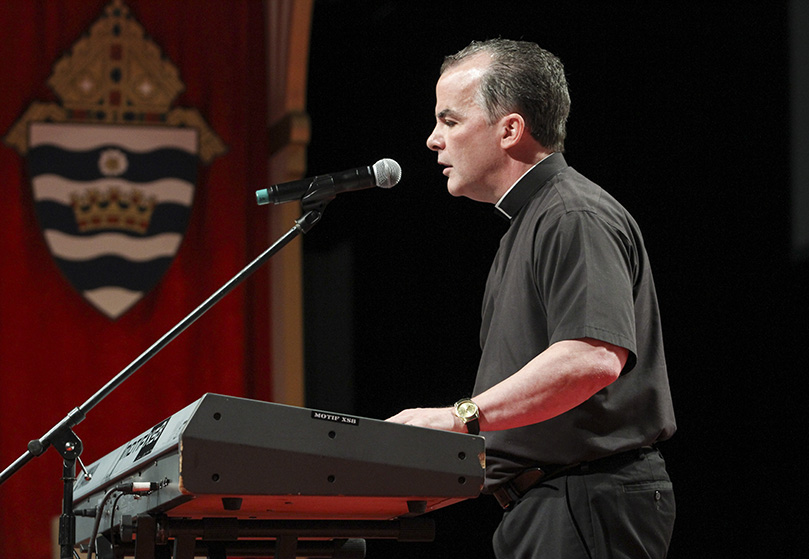 Father Mike Joly, pastor of St. Joan of Arc Church, Yorktown, Virginia, preached, sang and played the keyboards during his time in the English track. Father Joly has been totally blind since age six, and he became interested in music as teenager. Photo By Michael Alexander