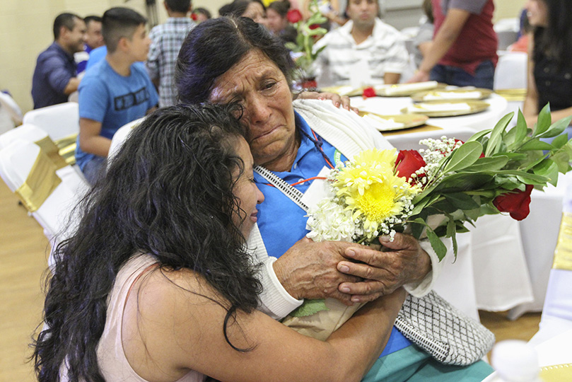 Even after their initial encounter when Maria Monroy, left, presented her 73-year-old mother, Juana Cruz, with a bouquet of flowers, Monroy continued an extended embrace with her mother at the table. Their last face-to-face was in 2001. Photo By Michael Alexander