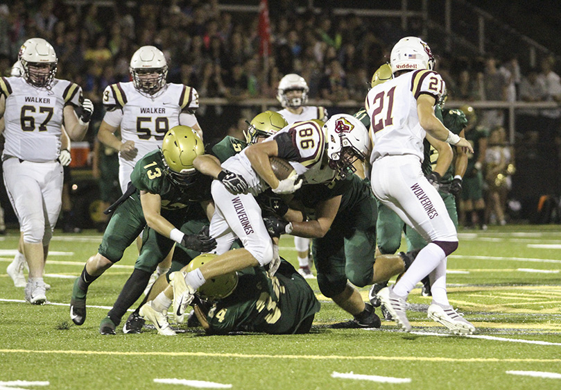 Pinecrest Academy defensive back Tripp Hochman and linebackers Alex Jeffords and Joey Kiernan gang tackle Walker wide receiver Cam Baker (#86) during the second half the Sept. 27 game. Photo By Michael Alexander