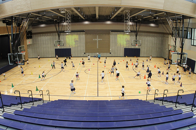 Students make use of the gymnasium inside the Cathedral of Christ the King's new Hyland Center during a physical education class. The wood surrounding the cross below is from the bleachers in the original Hyland Center. Photo By Michael Alexander