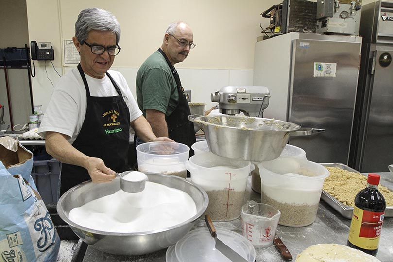 Humberto Guzman, president of the St. Oliver Plunkett Men's Club, rations the appropriate portion of sugar and chopped walnuts, two of the several ingredients that go into the making of the walnut filling. Ken Drake, background, was responsible for combining all the ingredients in a bowl under the Hobart electric mixer. Photo By Michael Alexander