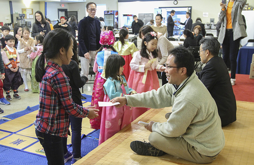 (Sitting on the stage, foreground to background) St. Andrew Kim Church parochial vicar Father Juchan Kim and pastor Father Kolbe Man Young Chung distribute envelopes, enclosed with a two-dollar bill, to the children for good luck in the New Year. Photo By Michael Alexander