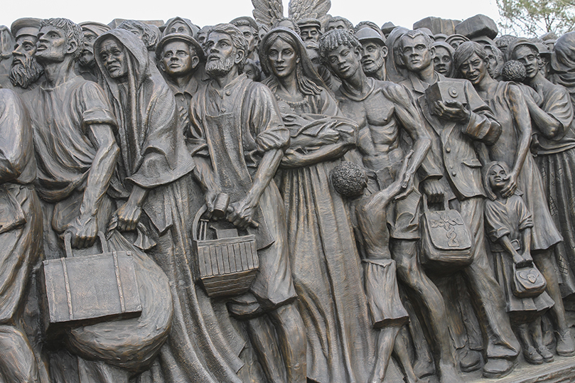 """The church's teachings on immigration are reflected in the """"Angels Unawares"""" sculpture that depicts more than 140 immigrants over different periods in history. The immigrants are closely packed on a boat with the Holy Family. The sculpture will be on display in the upper school quad at Holy Spirit Preparatory School, Atlanta, until Feb. 3. Photo By Michael Alexander"""