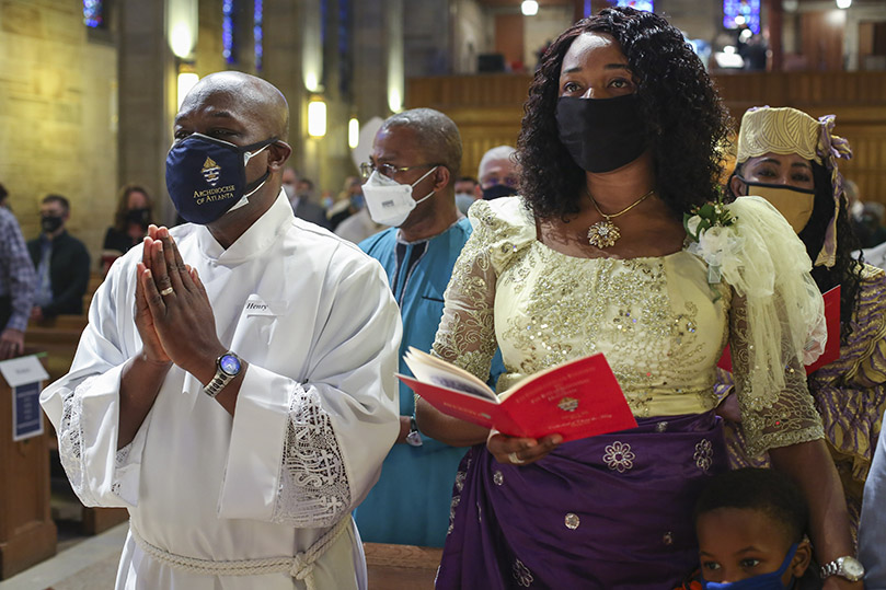 Dr. Henry Ohaya and his wife, Ihuoma, join others in the congregation in singing the processional hymn, Here I Am, Lord. Ohaya was one of seven deacon candidates ordained at the Cathedral of Christ the King, Atlanta, on Feb. 6. Photo By Michael Alexander