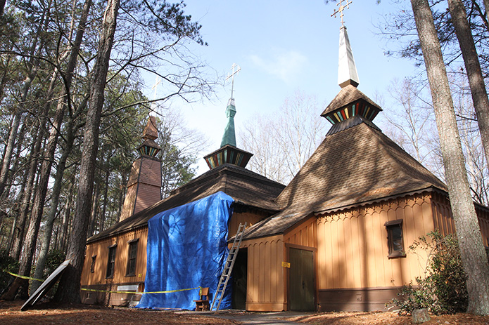 A blue tarp covers the side of Epiphany Byzantine Catholic Church, Roswell, where it incurred damage from an arson fire. The wooden church, marked by its Carpathian architecture style, was the first Byzantine Catholic Church in Georgia when it was dedicated in 1982. Photo By Michael Alexander