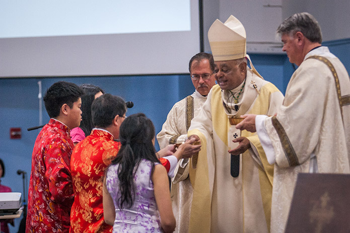 Archbishop Wilton D. Gregory receives the offertory gifts during the Nov. 19 Mass from the Chai family, dressed in traditional Chinese garb. Photo by Thomas Spink