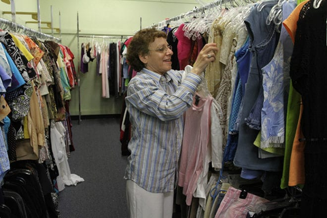 Lisa Malak, 60, hangs women's clothing on the floor racks at the St. Vincent de Paul Second Time Around Thrift Store, Lilburn, where she has worked for five years. Malak also resides at St. Mary's independent living site in Tucker. Photo By Michael Alexander