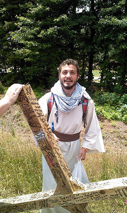 John Bessis, a Georgia Highlands College student from Rome, stands with the 6-foot cross he is carrying on a journey across Georgia to Myrtle Beach, S.C. He is making the pilgrimage to demonstrate the love of Jesus and to inspire others.  His experiences are shared on Facebook, at www.facebook.com/takingupthecross4christ. Photo courtesy of Patrick Gruber
