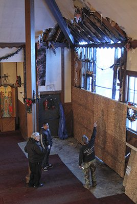 Father Philip Scott, left center, pastor of Epiphany Byzantine Catholic Church, observes the damage to the Roswell church's ceiling and wall with his maintenance crew. Early Sunday morning, Dec. 14, an arsonist allegedly set the house of worship on fire. Photo By Michael Alexander