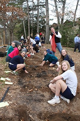 The eighth-grade class at St. Jude the Apostle School plants flower bulbs as part of the Daffodil Project on Dec. 19. The project aims to build a Holocaust memorial of 1.5 million daffodils around the world in memory of the 1.5 million children murdered during the Holocaust. They were planted between the rectory/church and the school along the path of the Stations of the Cross.