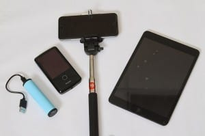 The portable equipment Rosemary Jean-Louis will take with her includes (l-r) a charger, a video recorder, a smartphone and selfie stick, and a digital tablet. Photo By Michael Alexander
