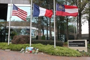 (L-r) The American, French and Georgia state flags blow in the wind at half-mast Nov. 15 as a makeshift memorial is displayed below them, just outside the French Consulate in Atlanta. Photo By Michael Alexander