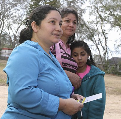 After a brief stopover at El Refugio, Sandra Portillo, foreground, stands with her mother and daughter as they prepare to return to the Charlotte, N.C., area. Portillo and other family members made the six-hour drive to visit her husband, who has been detained at the Stewart Detention Center for a year and a half. Each detainee gets one hour-long visit per week. Photo By Michael Alexander