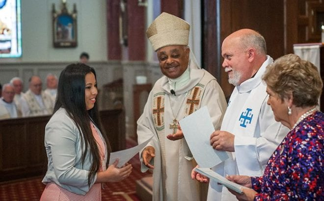 Arianna Ayala, left, Youth of the Year from Corpus Christi Church, Stone Mountain, receives her certificate at the annual Recognition Day Mass from Archbishop Wilton D. Gregory, second from left. Also on hand to congratulate her were Father William Williams, second from right, adviser to the AACCW, and Julie Pardo, AACCW president.