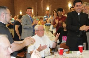 Father Frank Richardson, center, is given a standing ovation at the retirement party held by his parish, Good Shepherd Church. Father Ignacio Morales, right, served at the parish for five years. On the far left is the current parochial vicar, Father Jorge Carranza. The party included a slideshow and many guest speakers, who poked fun at the pastor's love for golf and Irish beer. Photo By David John Torrento Photography