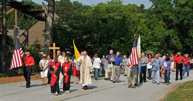Following the altar server with the processional cross, Father Greg Goolsby, left, pastor, and Deacon Fred Johns, right, lead the congregation from the church after Mass. Father Goolsby blessed the site. Photo By Lee Depkin