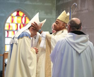 During the presentation of the pontifical insignia, Archbishop Wilton D. Gregory places the miter on the head of the new abbot Augustine Myslinski, OCSO. Photo By Michael Alexander
