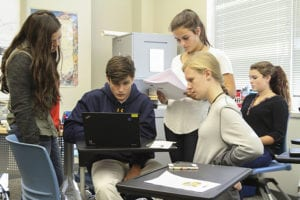 (L-r) Marist School junior student leader Claire Boerner observes sophomores Liam Dunn, Olivia Shutley, Lauren Jennings and Madelyn Jardina work on editing their public service announcement video on the issue of human trafficking. It was one aspect of the school's Oct. 13 Informed Discourse Day, a day for dialogue, discussion and debate exploring human trafficking. Photo By Michael Alexander